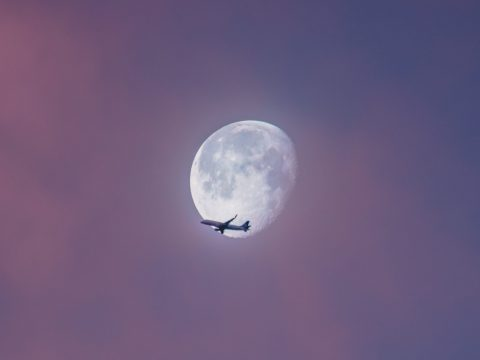 airplane against the moon