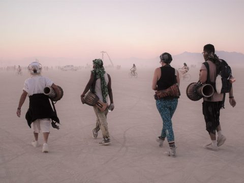 four people walking at burning man