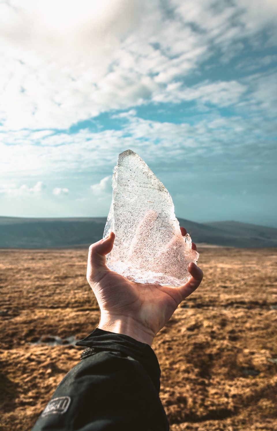man holding ice in the desert